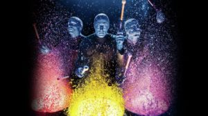 Blue Man Group drums on buckets lined with paint, creating cool visuals.